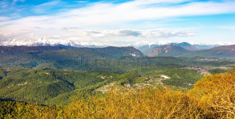 Widok przy zmierzchem na zielonej górkowatej dolinie z domami i wysokimi śnieżnymi górami na horyzoncie fotografia royalty free