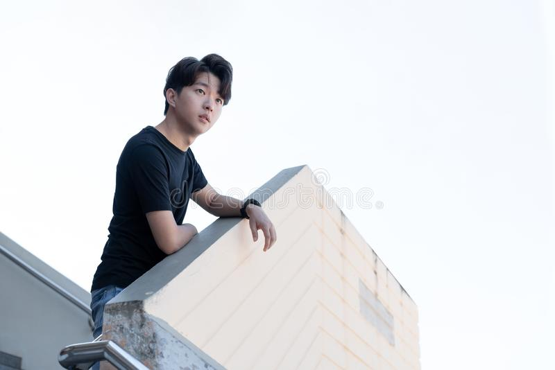Widok PRZYPADKOWY azjatykci młody człowiek pozuje na outdoors budynku krokach spod spodu odizolowywa na bielu fotografia royalty free