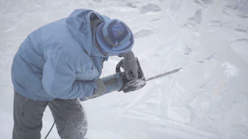 Widok rzeźbiarza cyzelowania lód ruch Rżnięty lód z piłą łańcuchową Cięcie i robi śnieżnej rzeźbie Siekać zamrażającą wodę z obraz stock