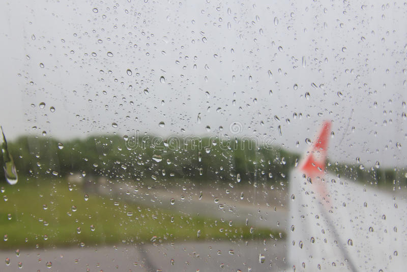 Widok skrzydło samolot przez nadokiennego moczy od podeszczowego (Zamazana tapeta) fotografia stock