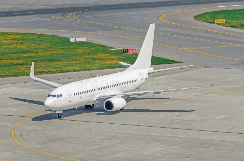 Widok sterowniczy pas startowy z białym pasażerskim samolotem na lotniskowym fartuchu i ślad zdjęcia royalty free