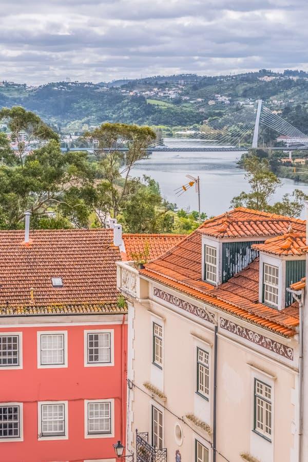 Widok tradycyjni klasyczni budynki z zamazaną Mondego rzeką i Rainha Santa Isabel mostem jako tło w Coimbra, obraz stock