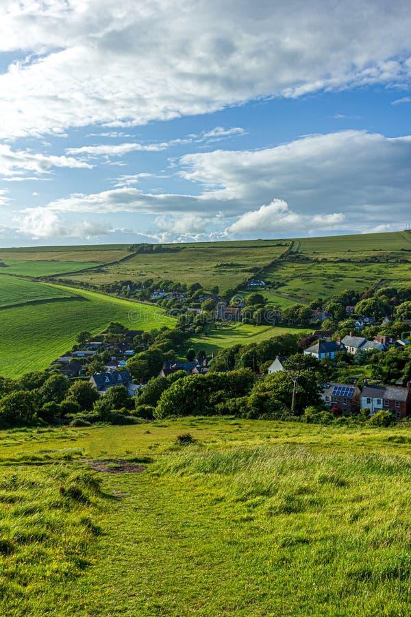Widok wioska Zachodni Lulworth od wzgórza pod majestatycznym niebieskim niebem i niektóre białymi chmurami obrazy royalty free