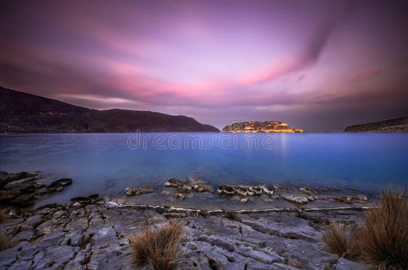 Widok wyspa Spinalonga przy zmierzchem z ładnymi chmurami i spokojnym morzem fotografia stock