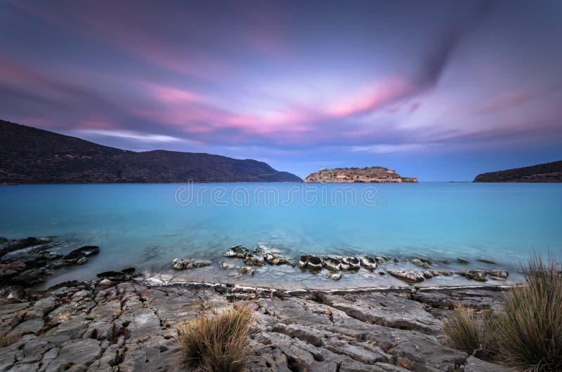 Widok wyspa Spinalonga przy zmierzchem z ładnymi chmurami i spokojnym morzem obraz royalty free