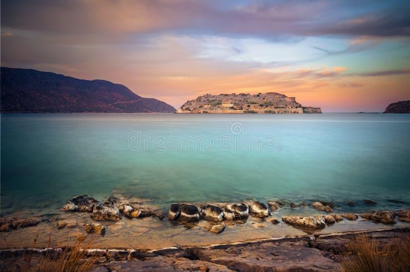 Widok wyspa Spinalonga przy zmierzchem z ładnymi chmurami i spokojnym morzem zdjęcia royalty free