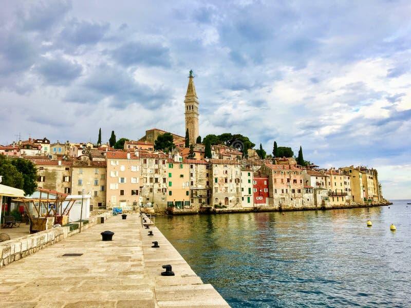 Widok wzdłuż boardwalk stawia czoło starego miasteczko Rovinj, Chorwacja Starzy colourful budynki i zegarowy wierza są linia hory obraz royalty free
