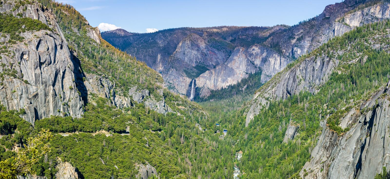 Widok Yosemite dolina z Merced rzecznym spływaniem przez wiecznozielonych lasów i Bridalveil Spada widoczny w tle; fotografia stock