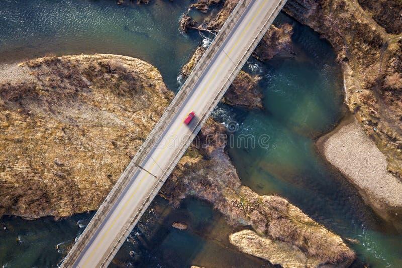 Widok z lotu ptaka bielu most z poruszającym czerwonym samochodem nad błękitne wody i kamienistymi wyspami zdjęcia royalty free