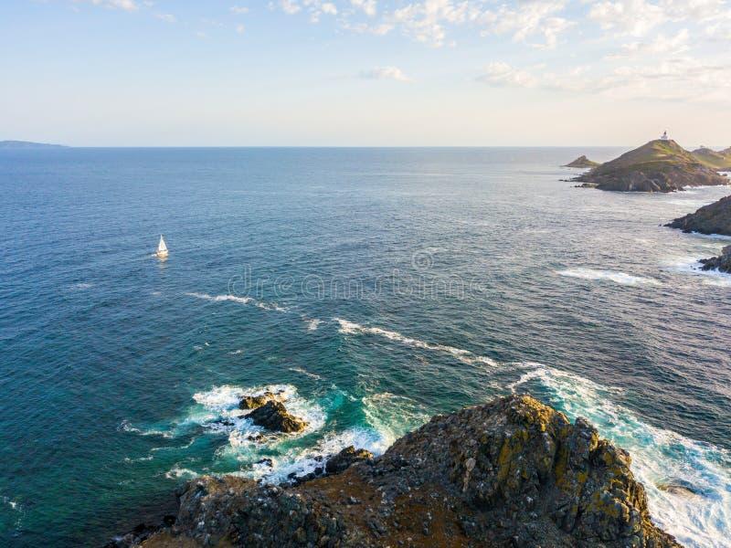 Widok z lotu ptaka Bloods wyspy latarnia morska i, Corsica, Francja: skały, fala i żaglówka, zdjęcia royalty free