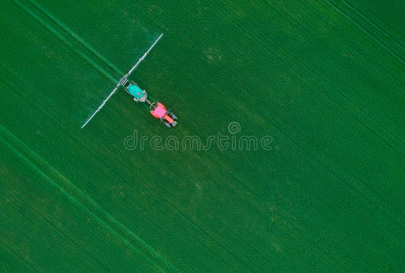 Widok z lotu ptaka ci?gnikowy opryskiwanie substancje chemiczne na ampu?y zieleni polu - wizerunek obraz royalty free