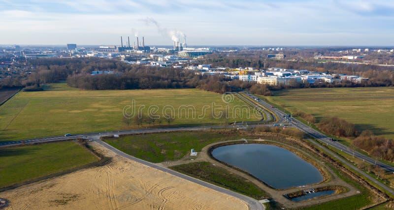 Widok z lotu ptaka deszczówka retencyjny basen z i przemysłowy miasto w tle drogami i wielkim łąkowym terenem zdjęcie stock