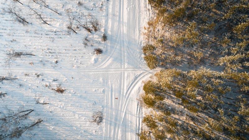 Widok z lotu ptaka drogowy omijanie przez śnieżystej zimy lasowego Odgórnego widoku zdjęcie stock