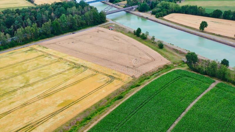 Widok z lotu ptaka kanału biegnącego przez pola, łąki i grunty orne w płaskim krajobrazie w północnych Niemczech fotografia royalty free
