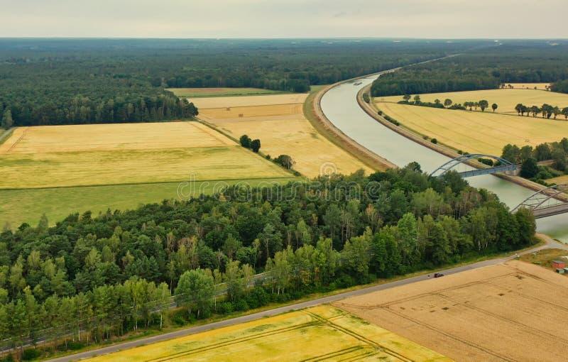 Widok z lotu ptaka kanału biegnącego przez pola, łąki i grunty orne w płaskim krajobrazie w północnych Niemczech obraz royalty free