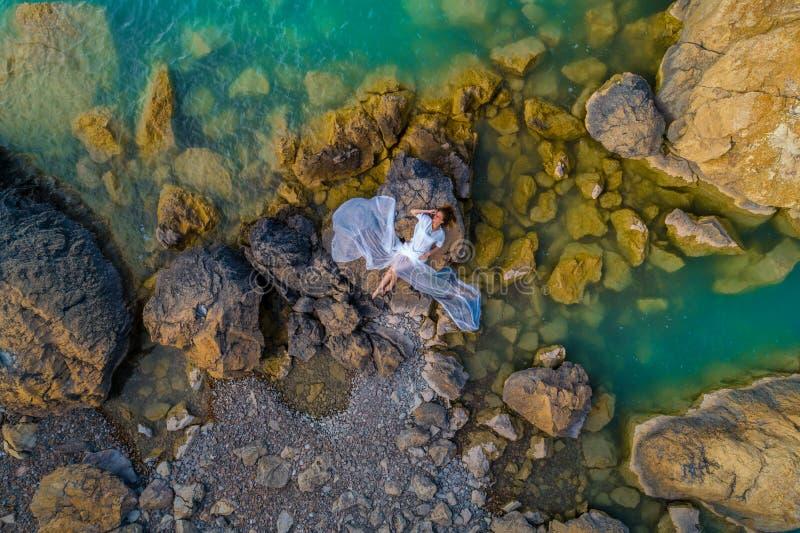 Widok z lotu ptaka młoda kobieta jest ubranym białą suknię na skałach Lata seascape z dziewczyną, plaża, piękne fale, skały, błęk zdjęcia stock
