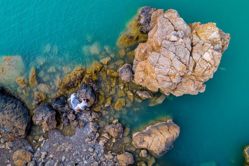 Widok z lotu ptaka młoda kobieta jest ubranym białą suknię na skałach Lata seascape z dziewczyną, plaża, piękne fale, skały, błęk fotografia royalty free