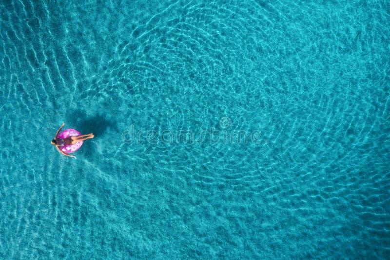 Widok z lotu ptaka młodej kobiety dopłynięcie na różowym pływanie pierścionku w przejrzystym turkusowym morzu przy wschodem słońc obraz royalty free