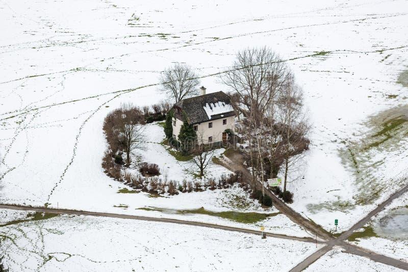 Widok z lotu ptaka na osamotnionym domu w polu zakrywającym śniegiem przy Salzburg fotografia royalty free