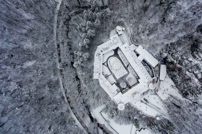 Widok z lotu ptaka ortodox monaster po środku śnieżnego lasu fotografia stock