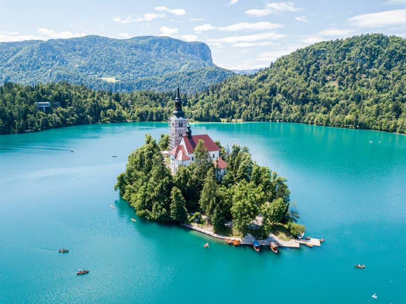 Widok z lotu ptaka otok, wniebowzięcie Mary kościół z wierza, iglica, i, na górze Krwawiliśmy jezioro, Slovenia zdjęcie stock