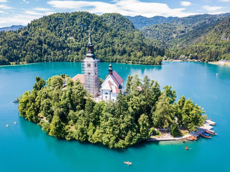 Widok z lotu ptaka otok, wniebowzięcie Mary kościół z wierza, iglica, i, na górze Krwawiliśmy jezioro, Slovenia obraz stock