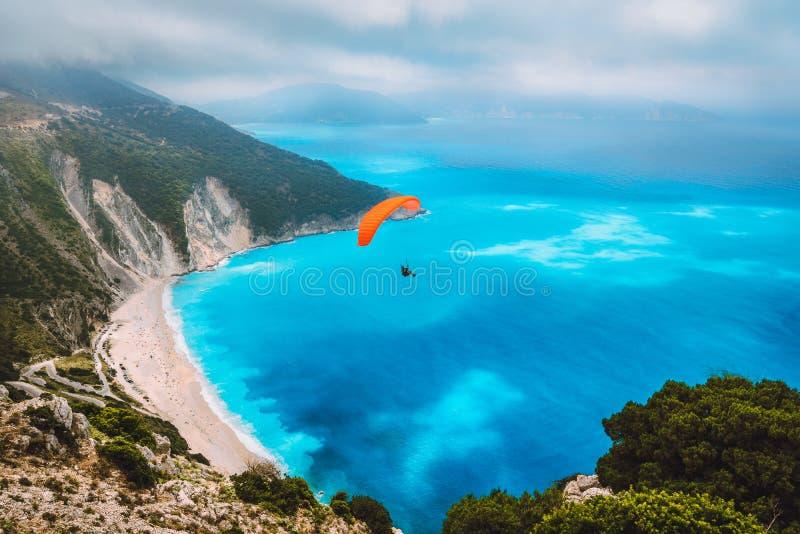 Widok z lotu ptaka paraglider lata nad wspaniałą Myrtos plażą Zadziwiający wodni kolory dalej i piękna linia brzegowa obrazy royalty free
