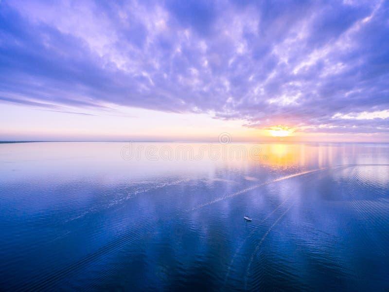 Widok z lotu ptaka piękny wschód słońca - osamotniona łódź w szerokim oceanie zdjęcia royalty free
