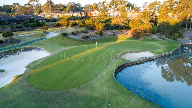 Widok z lotu ptaka pole golfowe zieleń z flaga, bunkiery i tam wodni zagrożenia otaczający drzewami w tle fotografia stock