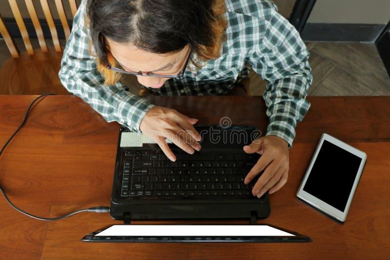 Widok z lotu ptaka pracownik używa laptop dla jego pracy w biurku przy biurem obraz royalty free