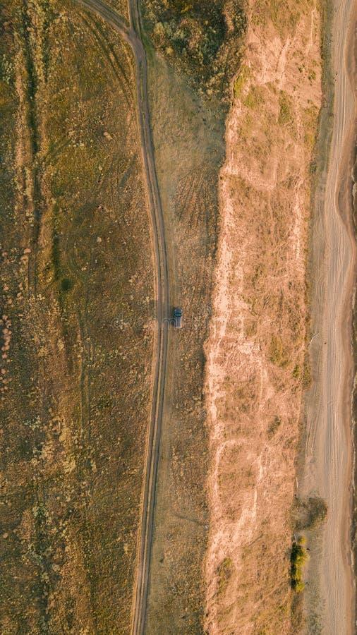 Widok z lotu ptaka samochód parkujący blisko wiejskiej drogi przy zmierzchem na plaży Piękny krajobraz z pustą wiejską drogą obrazy royalty free