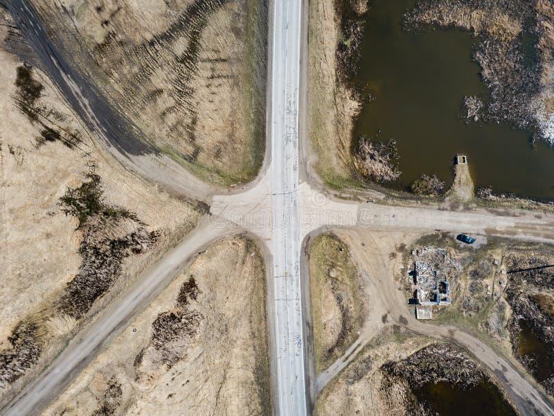 Widok z lotu ptaka skrzyżowanie asfaltu i ziemi drogi w polu daleko od dużych miast na jasnym wiosna dniu Droga zdjęcie royalty free