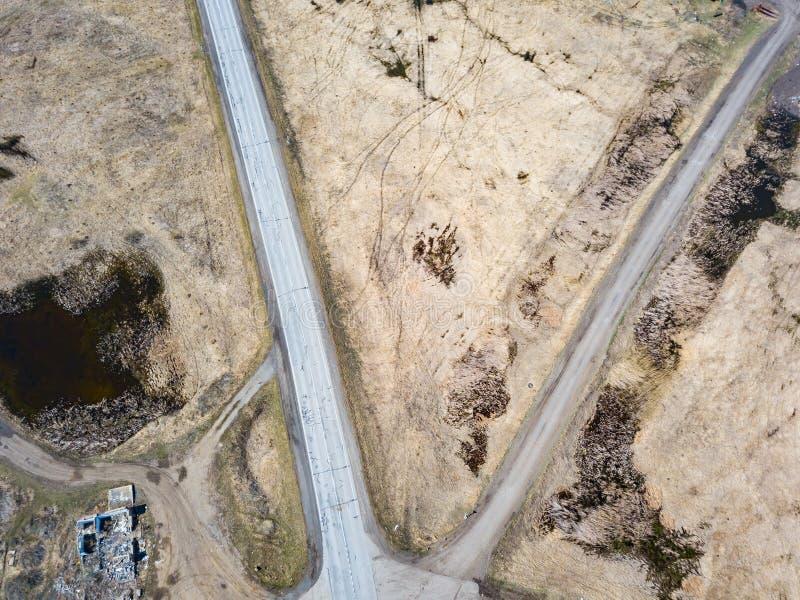 Widok z lotu ptaka skrzy?owanie asfaltu i ziemi drogi w polu daleko od du?ych miast na jasnym wiosna dniu Droga fotografia stock