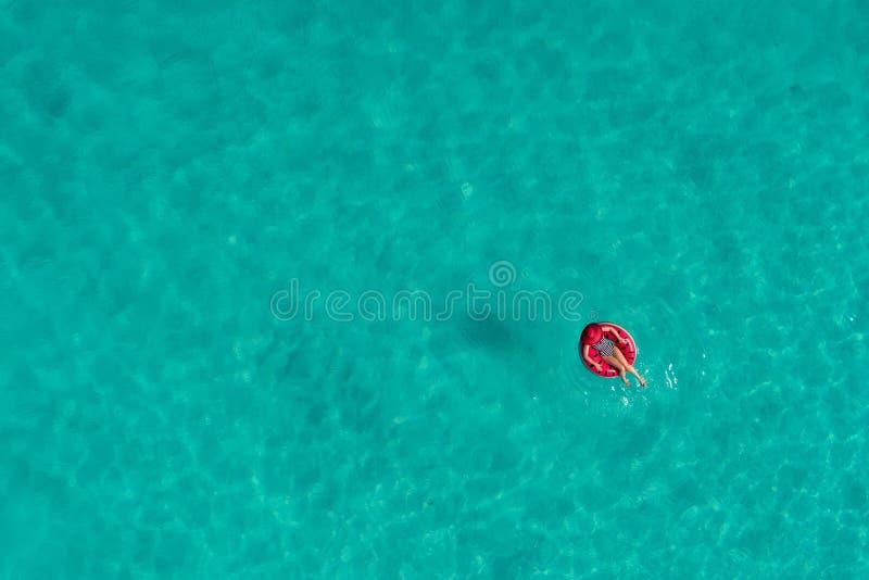 Widok z lotu ptaka szczupły kobiety dopłynięcie na pływanie pierścionku pączku w przejrzystym turkusowym morzu w Seychelles Lata  zdjęcia royalty free