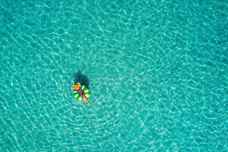 Widok z lotu ptaka szczupły kobiety dopłynięcie na pływanie pierścionku pączku w przejrzystym turkusowym morzu w Seychelles Lata  obrazy stock