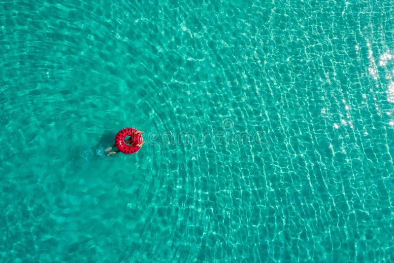 Widok z lotu ptaka szczupły kobiety dopłynięcie na pływanie pierścionku pączku w przejrzystym turkusowym morzu w Seychelles Lata  zdjęcia stock