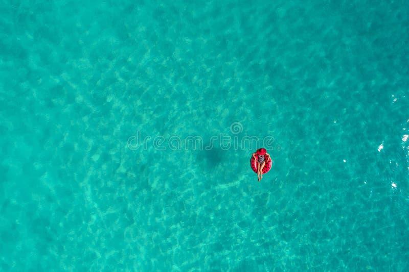 Widok z lotu ptaka szczupły kobiety dopłynięcie na pływanie pierścionku pączku w przejrzystym turkusowym morzu w Seychelles Lata  fotografia royalty free