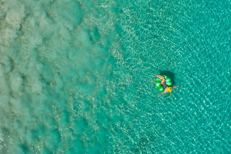 Widok z lotu ptaka szczup?y kobiety dop?yni?cie na p?ywanie pier?cionku p?czku w przejrzystym turkusowym morzu w Seychelles Lata  fotografia stock