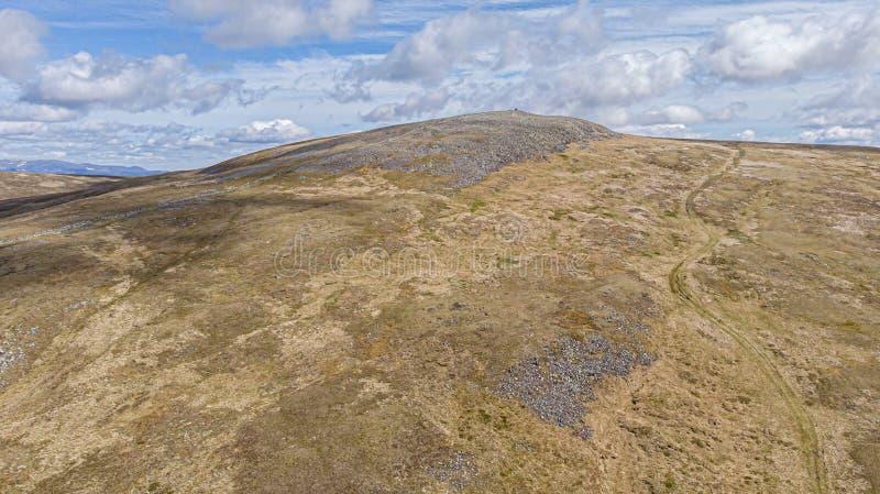 Widok z lotu ptaka Szkocki skalisty Munro szczyt z ?lad ?cie?k? pod majestatycznym bielem i niebieskim niebem chmurnieje zdjęcie royalty free
