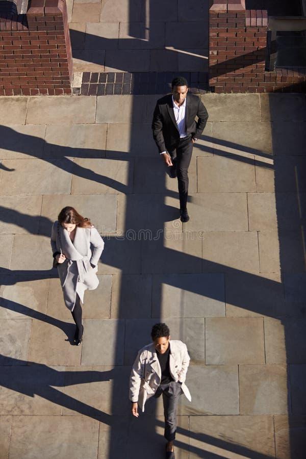 Widok z lotu ptaka trzy ludzie biznesu chodzi w ten sam kierunku na pogodnej miastowej ulicie, pionowo zdjęcia royalty free