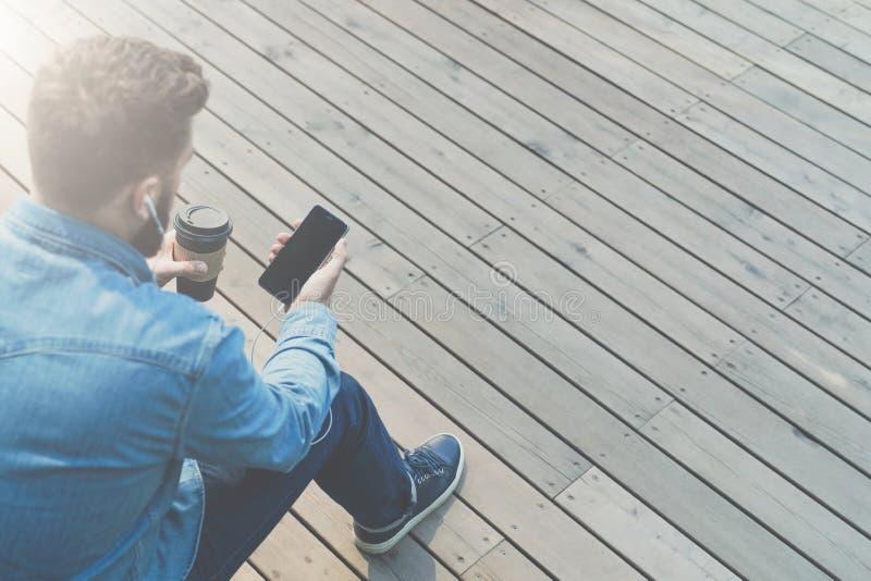 widok z powrotem Modnisia mężczyzna jest siedzieć outside, pić kawowy i używać smartphone, Facet trzyma w rękach siedzi, dzwoni zdjęcia royalty free