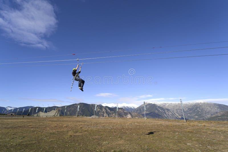 Widok z tyłu młodego mężczyzny jeżdżącego na linii ZIP na niebieskie niebo fotografia stock
