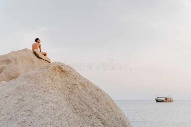 Widok z tyłu niekoszulnego mężczyzny szukającego spokoju siedzącego na skałach w Koh Tao, Tajlandia zdjęcia royalty free