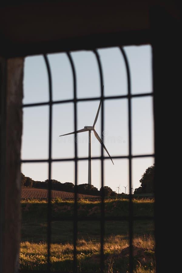 Widok z wewnątrz okno naturalna powierzchowność i wiatraczka w tle na złotym zmierzchu Czy?ci i energia odnawialna zdjęcia stock