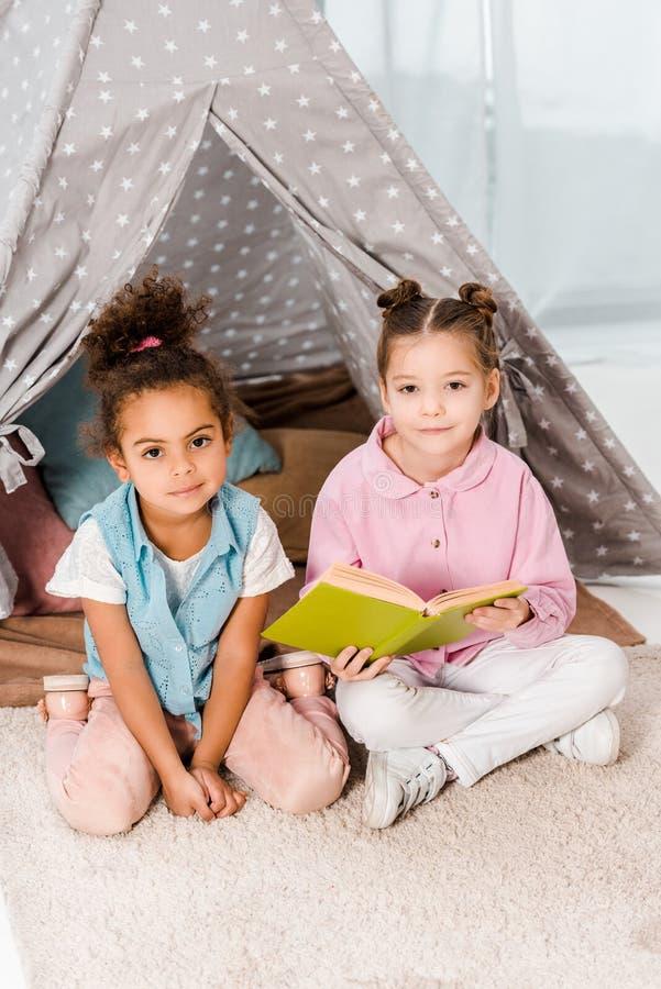 widok z wysokim kÄ…tem sÅ'odkich wieloetnicznych dzieci siedzÄ…cych na dywanie z książkÄ… i uÅ›miechajÄ…cych siÄ™ zdjęcia stock