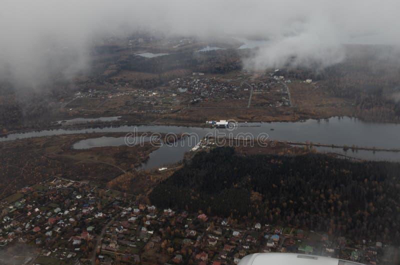 Widok ziemia od samolotu Przy wierzchołkiem białe chmury przy dnem rzeka, chałupy, las, rzeczny molo fotografia royalty free