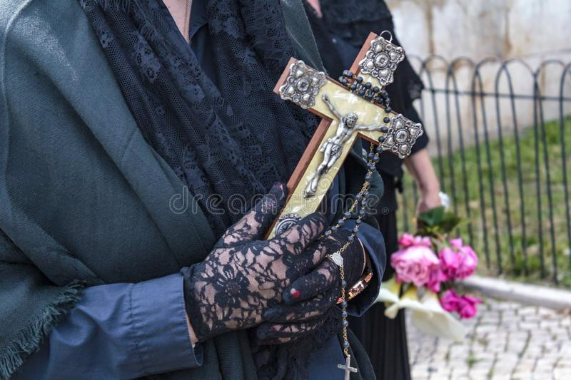 Widow hands holding a religious cross and a rosary royalty free stock photography