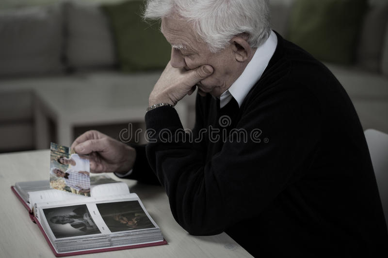 Widower remembering deceased wife. Widower looking at the photos and remembering deceased wife stock images