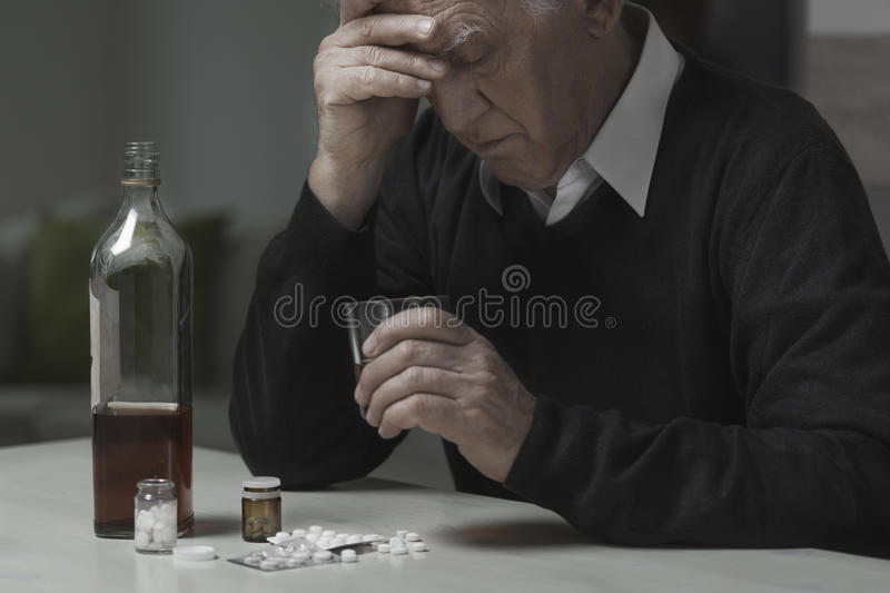 Widower use drugs and alcohol. Heartbroken widower use drugs and alcohol to kill sadness stock photography
