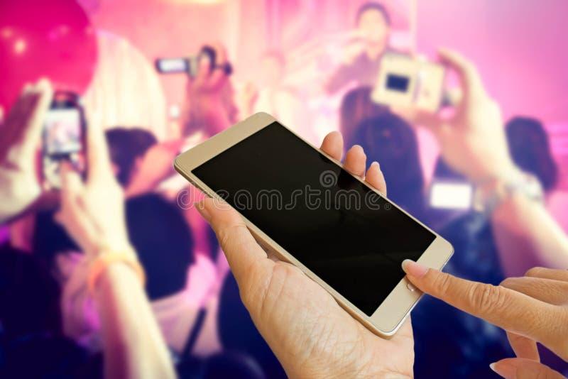 Widownie trzymają mądrze telefon brać fotografii muzycznego zespołu obrazy royalty free